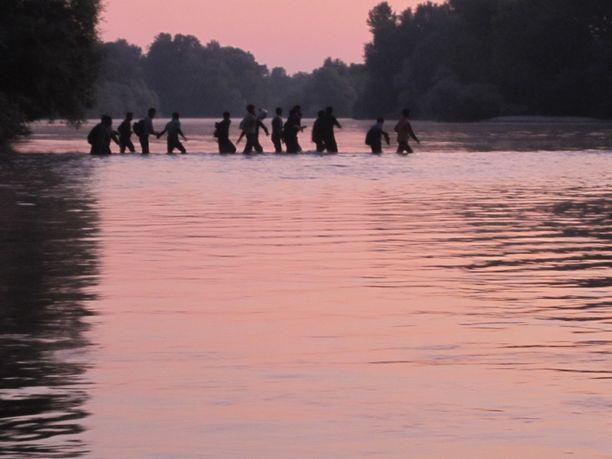 Mustaluoto on kuvannut siirtolaisia ylittämässä Evrosjokea kesällä matalan veden aikaan. Tilanne voisi olla kuin suoraan Mustaluodon kirjasta.