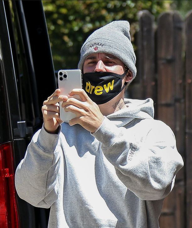 Justin Bieber kuvasi keskittyneesti kasvomaskinsa takaa.