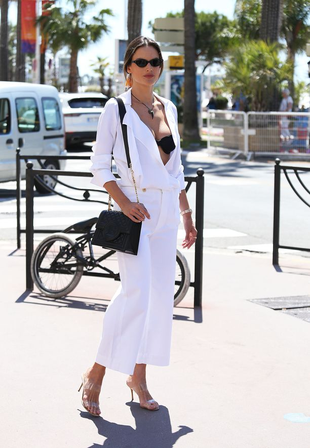 Alessandra Ambrosio yhdistää leveät valkoiset lahkeet klassisesti rentoon paitapuseroon. Mustat asusteet tekevät asusta skarpin - rakastamme myös hiuksiin sidottua huivia!