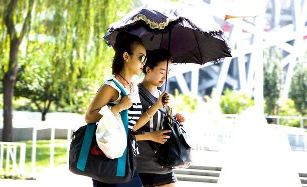 Kiinalaisnaiset suojautuvat auringolta ja savusumulta varjolla.