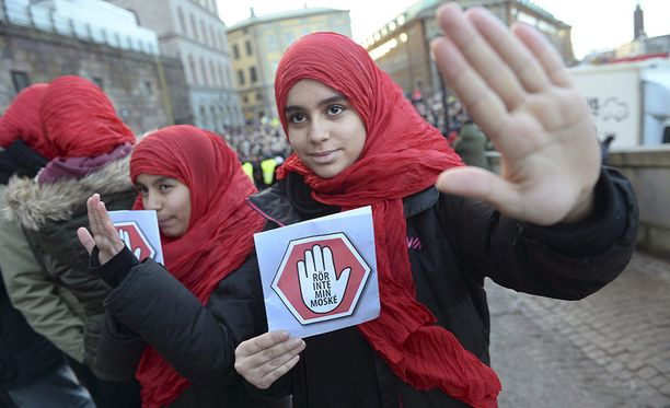 """Kaksi nuorta tyttöä kantaa kylttejä, joissa lukee: """"Älä koske moskeijaani"""". He osallistuivat tammikuussa 2015 mielenosoitukseen Tukholmassa sen jälkeen, kun muslimeita vastaan oli tehty useita iskuja."""
