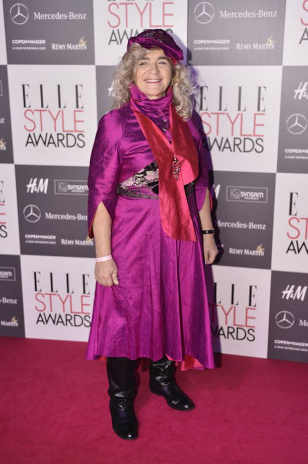 Taiteilija Miina Äkkijyrkkä puki ylleen värikkään pinkin mekon ja matsaavat asusteet.
