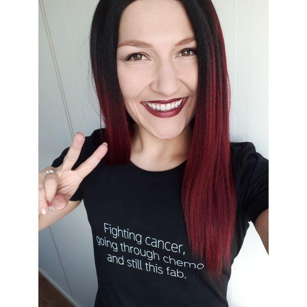 Kuvassa Mia Männistö poseeraa voimapaidassaan. Mian mukaan Janiinan ystävyys ja vertaistuki on ollut korvaamatonta rintasyövän aikaan.