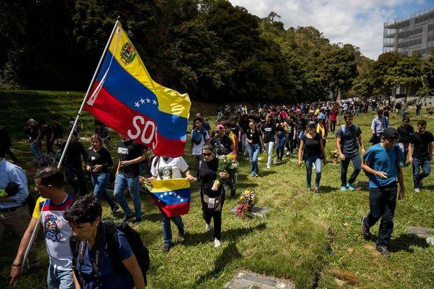 Ryhmä ihmisiä kokoontui hautausmaalle Caracasiin muistamaan niitä, jotka saivat surmansa vuosien 2014-2017 mielenosoituksissa. Yksin viime vuonna ainakin 120 ihmistä sai surmansa ja tuhansia loukkaantui.