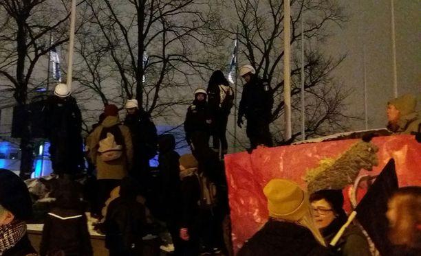 Mustin lipuin varustautuneet protestoijat pyrkivät paremmille paikoille. Poliisi näytti selvittävän tilanteen puhumalla.