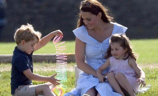 Herttuatar Catherine sylissään prinsessa Charlotte. Prinssi George näyttää äidilleen leluaan.