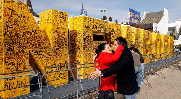 """Kosovolaiset kokoontuvat itsenäisyyspäivänä pääkaupunki-Pristinaan itsenäistymisen kunniaksi pystytetyn """"Newborn""""-monumentin luokse."""