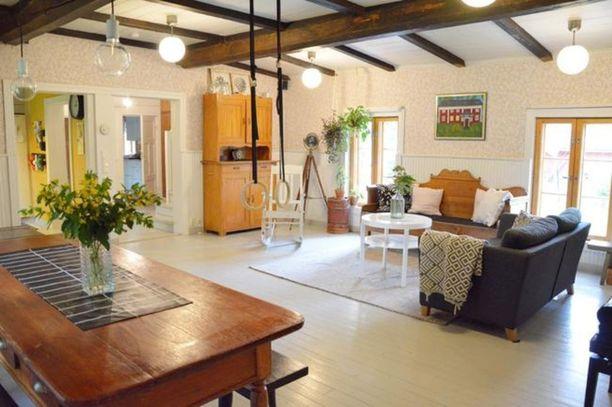 Tämä olohuone on kaunis yhdistelmä uutta ja vanhaa. Keinutuoli, pöytä ja puusohva vievät ajatuksissa vuosikymmenten taa, kun taas matto, voimistelurenkaat, sohva ja lamput ovat tätä päivää.