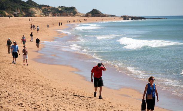 Päiväkävelijöitä nautiskeli Albufeiran hiekkarannalla.