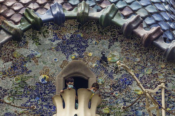 Pojilla on kasvomaskit päällään heidän kurkkiessaan Antoni Gaudín suunnitteleman Casa Batllón parvekkeelta Barcelonassa.