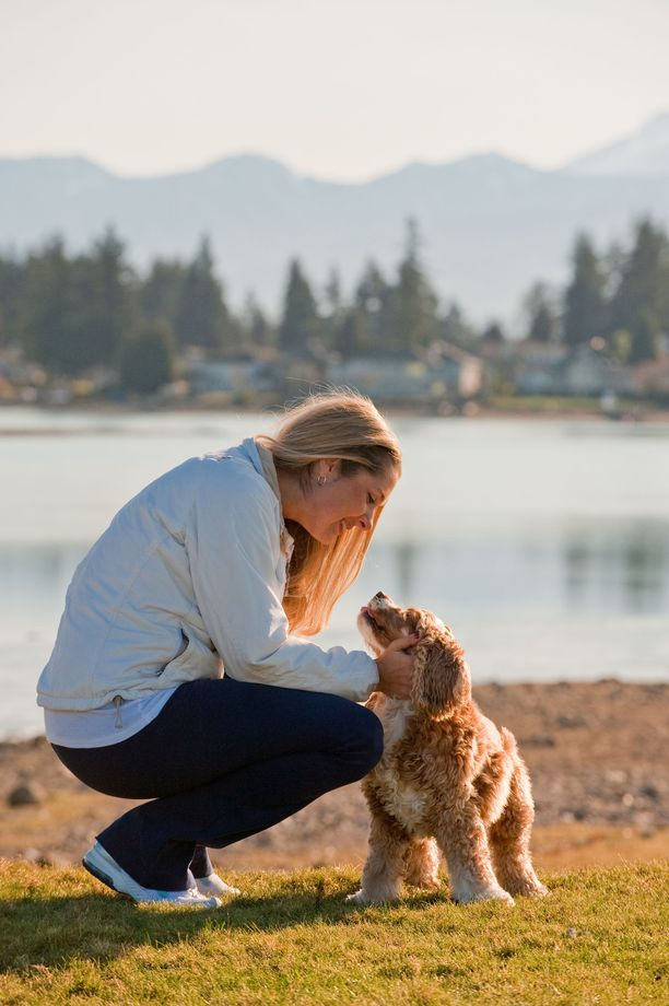 A young woman and her dog at the lake