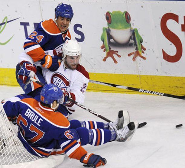 Oilers-pelaajat Steve Staios ja Gilbert Brule yrittävät pysäyttää Montrealin Kyle Chipchuraa, mutta tämä jatkaa pelaamista kieli keskellä suuta.