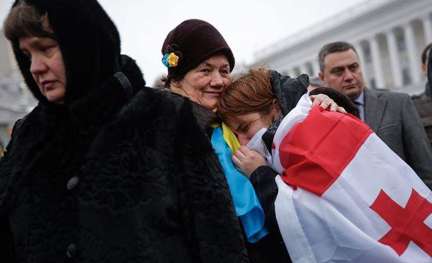 Naiset surivat sotilaan hautajaisissa Kiovassa.