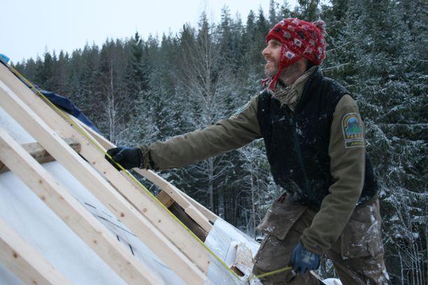 Kuvassa Mick Walsh tekemässä kattoa. Tällä hetkellä talo on katontekovaiheessa. Seuraavaksi siihen laitetaan eristeeksi olkipaalit ja sisä- ja ulkoseiniksi savea.