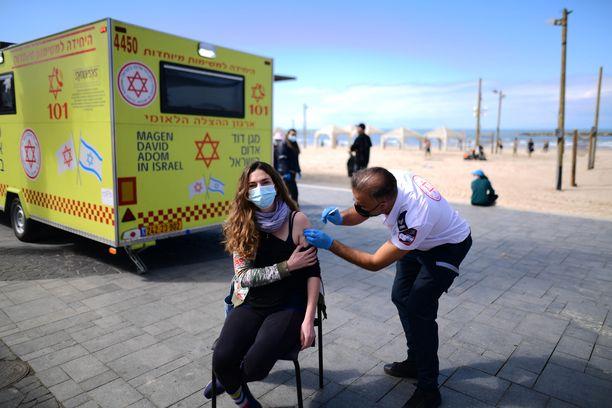 Nainen sai koronarokotteen Israelissa väliaikaisessa rokotuskeskuksessa Tel Avivissa Israelissa lauantaina.