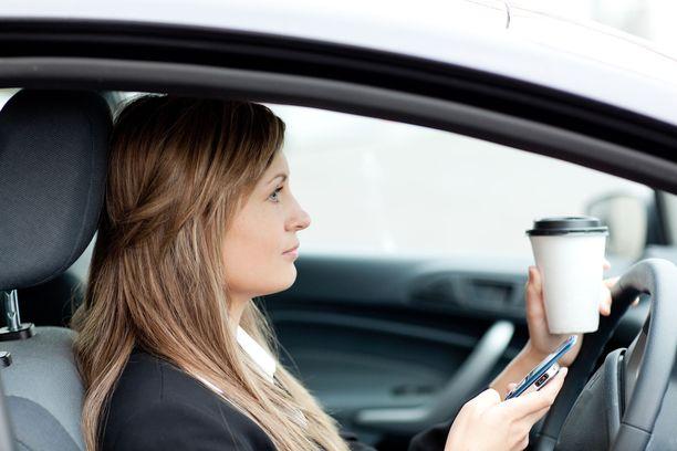Kännykkää ei saa ajon aikana pitää kädessä, mutta kahvikuppia ei ole kielletty. Kuvituskuva.