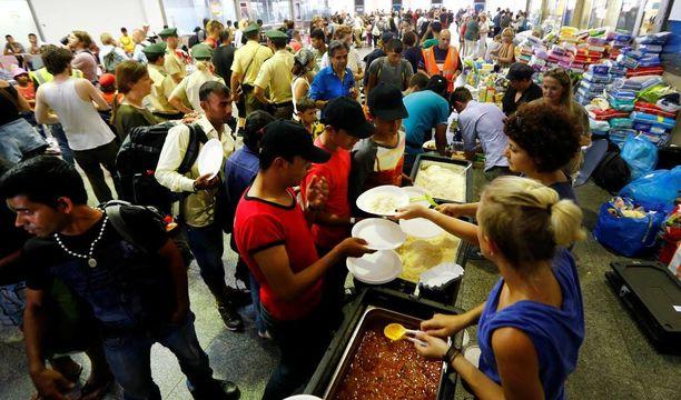 Vapaaehtoiset jakoivat ruokaa maahan saapuneille pakolaisille Münchenin rautatieasemalla. Arkistokuva viime syyskuulta.