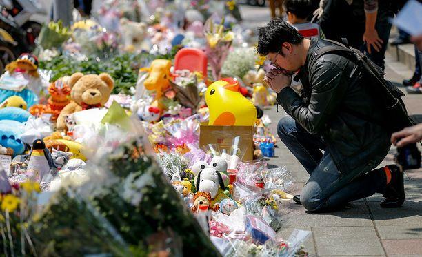 Mies hiljentyi tytön muistoksi tuotujen kukkien äärelle Taipeissa viime vuoden maaliskuussa.