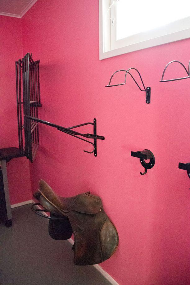 Kodinhoitohuoneessa on teollisuuspesukone ja kuivausrumpu hevosen loimille ja tallivaatteille. Kuvassa näkyvät seinään kiinnitetyt satulatelineet.