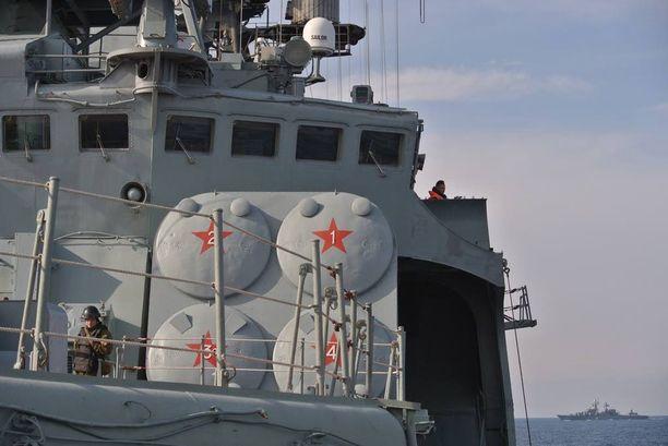 Venäjän laivaston jäsen vartioi hävittäjäaluksen kannella. Taustalla näkyy laivaston lippulaiva Varjag.