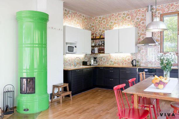 Olohuone yhdistyy tähän avokeittiöön, jossa on uskallettu käyttää värejä. Keittiön seinien tapetissa on samaa retrohenkeä kuin ikkunakehyksissä. Tässä tilassa voiton vie silti vihreä pönttöuuni, jota ei voi olla huomaamatta.