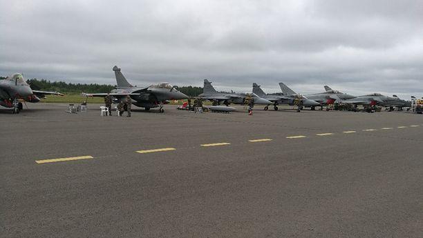 Hävittäjien rivistöä lentokentällä, vasemmalla kaksi Rafale-hävittäjää ja Gripen.