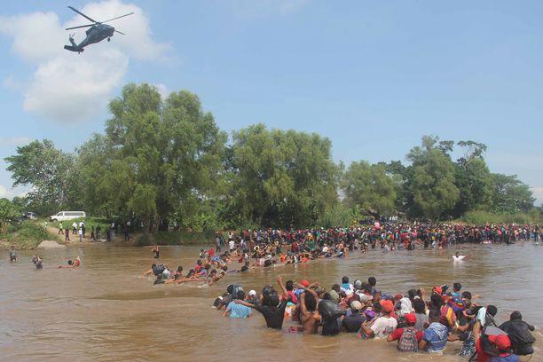 Kohti Yhdysvaltoja marssivia siirtolaisia ylittämässä jokea Guatemalassa.