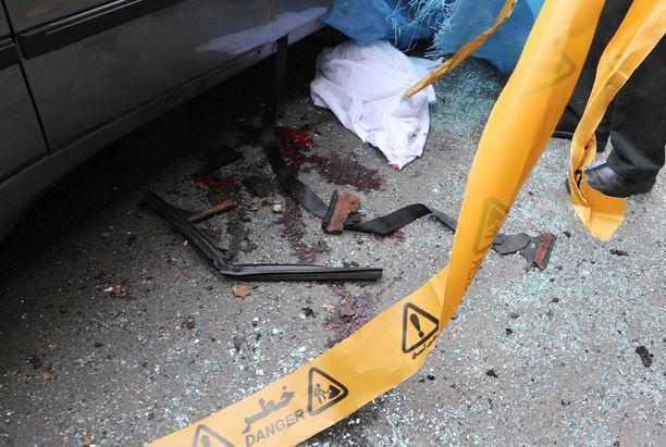 Veritahroja Mostafa Ahmadi Roshanin auton vierellä pommi-iskun jälkeen tammikuussa 2012. Ahmadi Roshan oli yksi viidestä salamurhatusta tutkijasta.