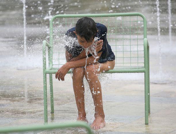 Lapsi viilentyy suihkulähteessä Albanian pääkaupungissa Tiranassa.