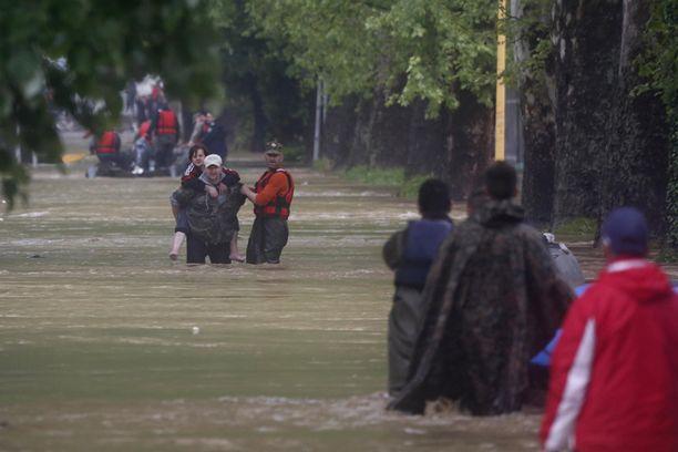 Mies auttaa naista pois tulva-alueelta Bosnian Maglaj-kaupungissa, noin 150 kilometriä Sarajevosta pohjoiseen.