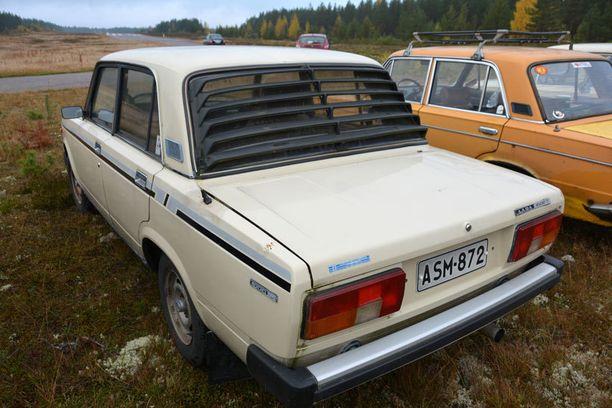 Lada-mies Jussi Kulonen ja Kulosen auto, jossa on yhä maahantuojan eli Konelan liimaamat vauhtiraidat sivuissa ja ritilä takaikkunassa.