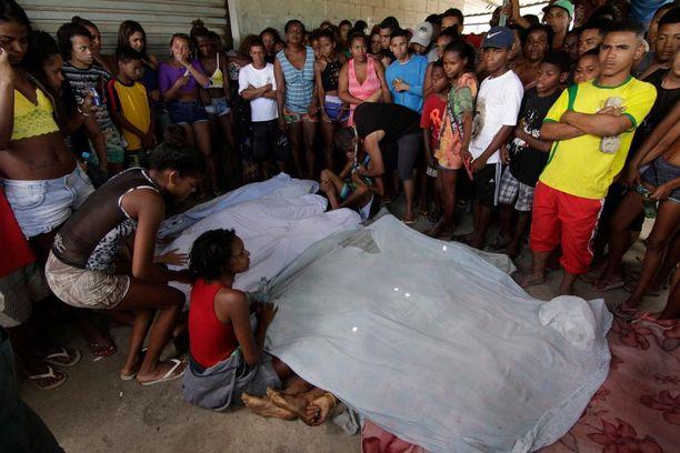 Sukulaiset ja ystävät kerääntyivät tapettujen nuorten ruumiiden äärelle sunnuntaina.