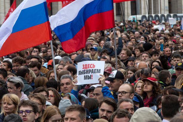 """Mielenosoituksessa vaadittiin vapaita vaaleja 10. elokuuta Moskovassa. Kyltissä lukee: """"Täällä äänestämme me!"""""""