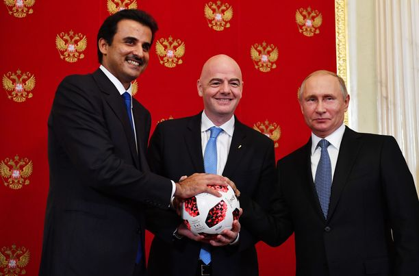 Qatarin emiiri Tamim bin Hamad Al Thani vastaanotti symbolisen kisapallon Venäjän presidentti Vladimir Putinilta edellisen MM-turnauksen päätyttyä. Keskellä FIFA:n puheenjohtaja Gianni Infantino .