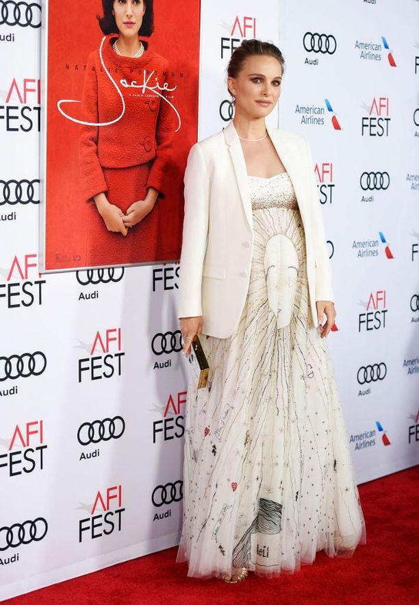 Pelkistetty valkoinen jakku tasapainottaa Natalia Portmanin runsaasti koristeltua ja liehuvaa mekkoa.