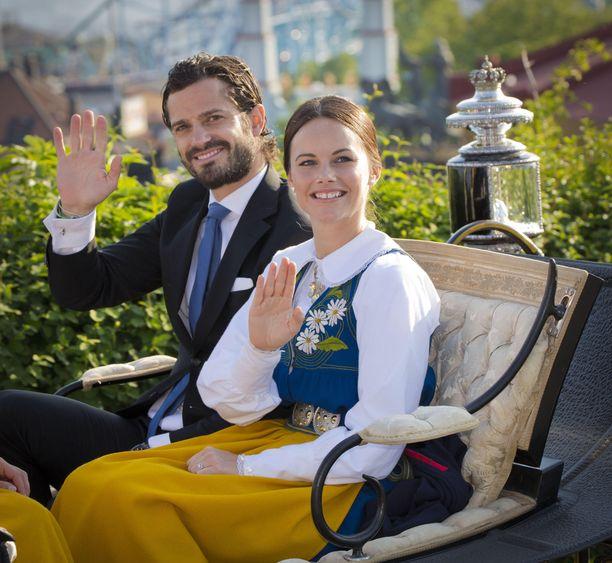 Prinssi Carl Philip vilkuttaa rakkaansa kanssa vankkureissa vuonna 2015.