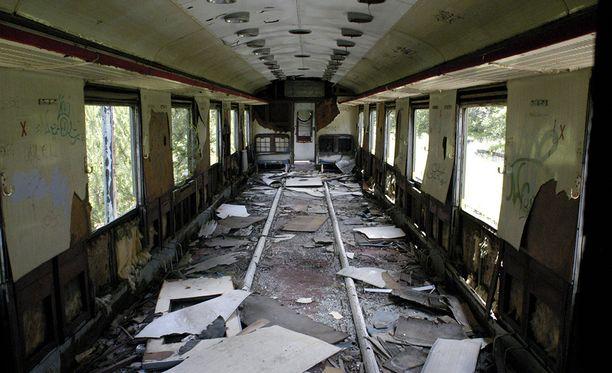 Asemalla on myös rappeutuneita junavaunuja.