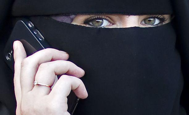 Niqabia käyttävä nainen puhui puhelimessa lähellä Pariisia syyskuussa 2011. Ranskassa huivin käyttämisestä voidaan rankaista sakolla.