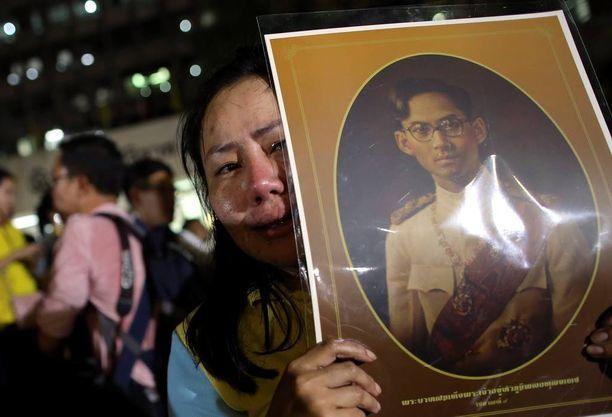 Nainen piti kuninkaan kuvaa ja itki Sirirajin sairaalan edessä Bangkokissa.