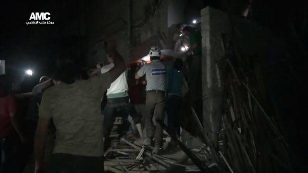 White Helmets -siviilipelastajat etsivät ihmisiä keskiviikkoiltana talojen raunioista Aleppossa.