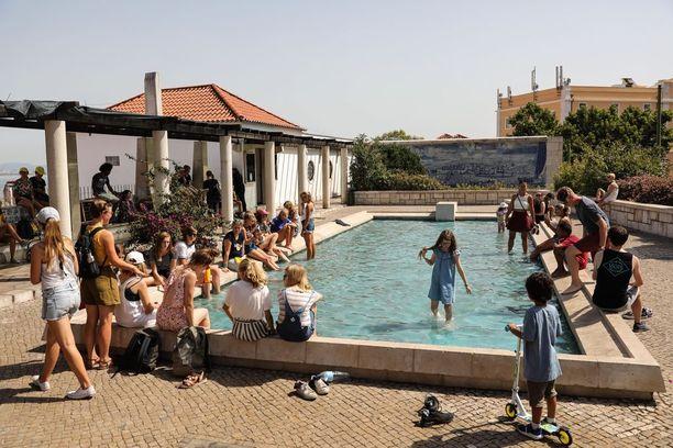 Ihmiset vilvoittelevat suihkulähteessä Lissabonissa.