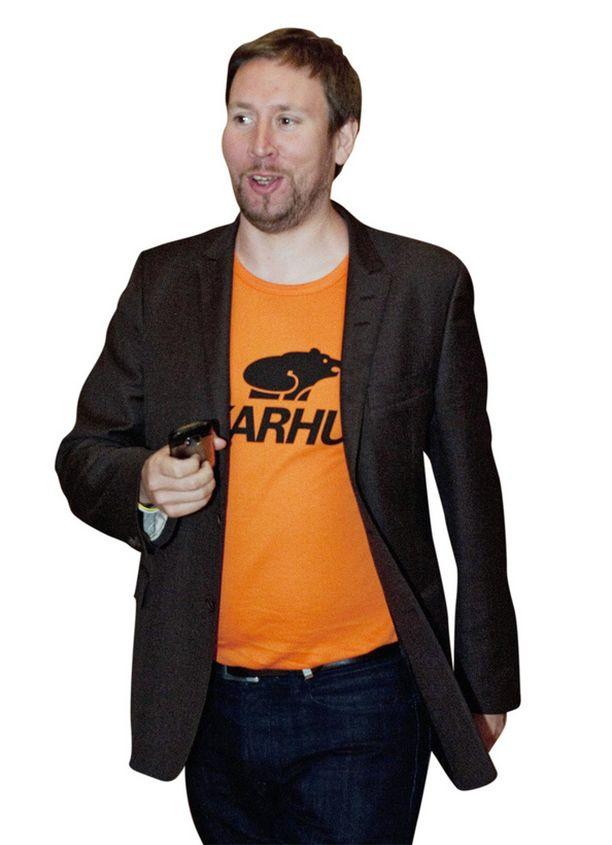 RENTO JA VÄRIKÄS Paavo Arhinmäki pukeutui räikeään t-paitaan työpaikalleen eduskuntaan. Arhinmäki nähdään usein rennoissa vaatteissa. Esimerkiksi Savonlinnan oopperajuhlilla mies säväytti punaisissa tennareissa.