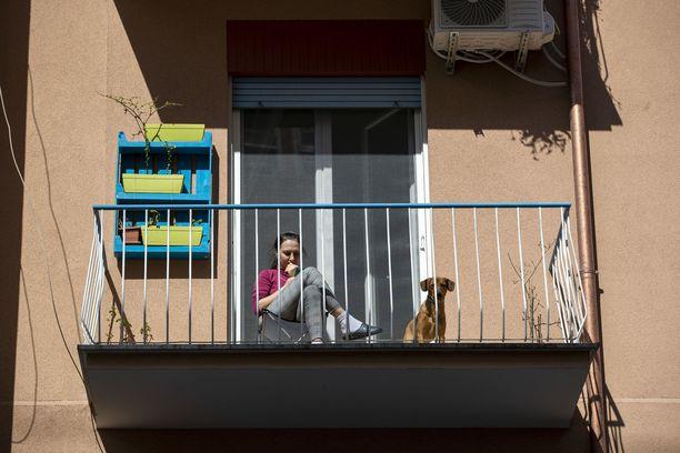 Karanteenissa oleva nainen istuu parvekkeella Roomassa. Italiassa todettiin eilen 5 986 uutta koronavirustartuntaa.