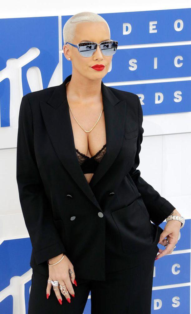 Amber Rose oli pukeutunut tummaan pukuun, mutta takin alta näkyi pintaa.