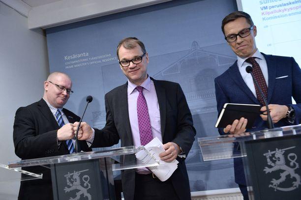 Jari Lindström, Juha Sipilä ja Alexander Stubb riemuitsivat yhteiskuntasopimuksen hyväksymisestä nyrkkitervehdyksellä tiedotustilaisuudessa 2016.