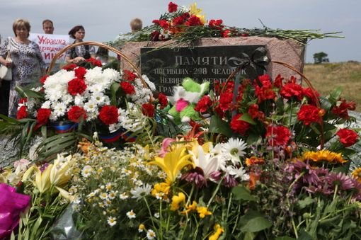 Ihmiset toivat kukkia muistomerkille koneen putoamispaikalla Grabovessa Donetskin alueella.