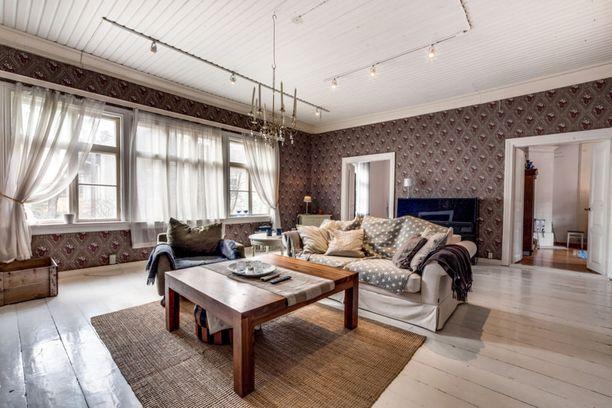 Näin isoon olohuoneeseen sopii loistavasti jykevä puupöytä. Iso sali vaatii valoa ja sen takaa seinärivistö ikkunoita.