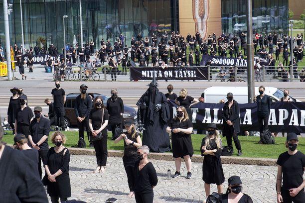 Mielenosoittajat seisoivat riveissä mustiin pukeutuneina.