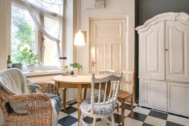 Pieni ruokailutila ikkunan vieressä on niin kotoisa kun olla ja voi. Eripariset vanhat tuolit ja korituoli tekevät kokonaisuudesta rennon, viltit ja taljat talvisen perhmeän.