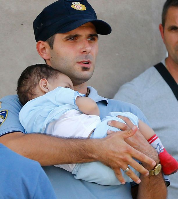 Syyrialaislapsi pääsi kroatialaispoliisin syliin.